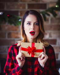 Young redhead woman with gift box at kitchen. Holiday time image