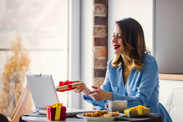 Beautiful young businesswoman have a coffee break while sitting indoors at home in Christmas time. Concept of work with startup business in Holiday time