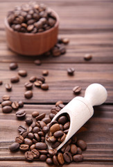 Coffee beans in wood spoon on brown background.