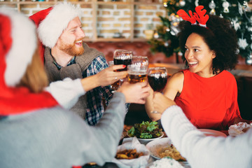 Friends drinking alcohol and having dinner for Christmas eve at home. Christmas holidays concept.