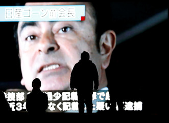 Passersby are silhouetted as a huge street monitor broadcasts news reporting ousted Nissan Motor chairman Carlos Ghosn's indictment and re-arrest in Tokyo