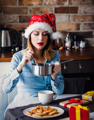 Beautiful young woman sitting at kitchen with pan and spoon around present gifts. Christmas time