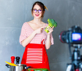 Young caucasian blogger woman cooking Vegan food at camera for Video-sharing website. Home location at kitchen
