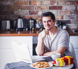 handsome man with cup of tea or coffee and laptop computer sitting at kitchen in Christmas time