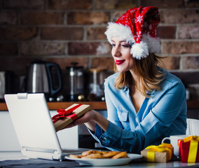 Beautiful young businesswoman in Santa Claus hat sitting and working with laptop. Concept of work with startup business in Christmas time