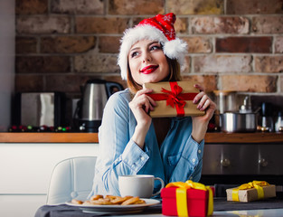 Beautiful young woman in Santa Claus hat sitting at kitchen with present gifts. Christmas time