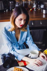 Beautiful young photographer have a coffee break while sitting working with camera and laptop. Concept of work with startup business in Christmas time