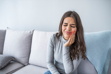 Beautiful Young Woman Suffering From Terrible Strong Teeth Pain, Touching Cheek With Hand. Female Feeling Painful Toothache. Dental Care And Health Concept