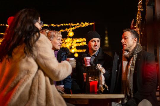 Man cheering to friends at Christmas market, Zagreb, Croatia.
