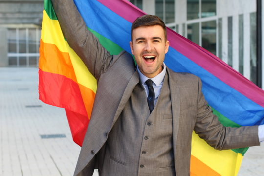 Happy businessman holding the rainbow flag