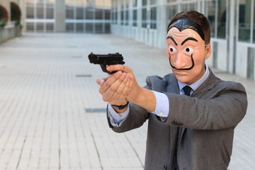 Businessman with mask holding a gun