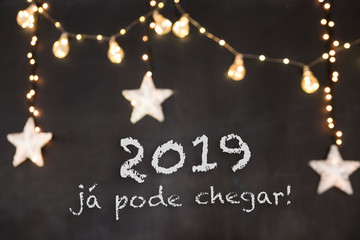 """2019 já pode chegar"" in portuguese means ""2019 can already arrive"" in black background with blurred stars and light."