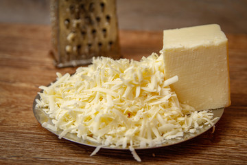 Grated cheese on metal plate on wooden table ready for pizza