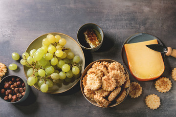 Wine snack. Cheese, grapes, nuts, cheese crackers cookies, honeycombs with knife over dark texture background. Flat lay, space