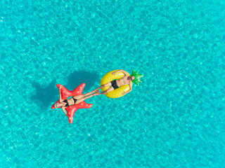 Aerial view of man and woman floating on inflatable mattresses touching feet.