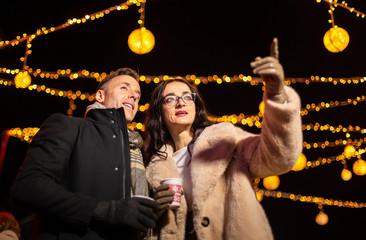 Couple pointing to decoration at Christmas market. Zagreb, Croatia.