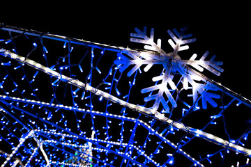 Glowing snowflakes and light stripes on dark, romantic night sky background. Beautiful Christmas market and decorations in city center.