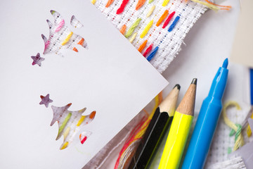 Creative workshop for kids. Sharp coloured drawing pencils, markers on table. Embroidery fabric with hand embroidered colorful elements. Kids learning to do creative crafts at school, cut decorations.