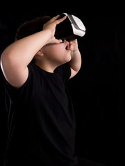 Fotobehang womenART Boy wearing a virtual reality glasses surprised by what he is seeing in the simulation or game, isolated on black background