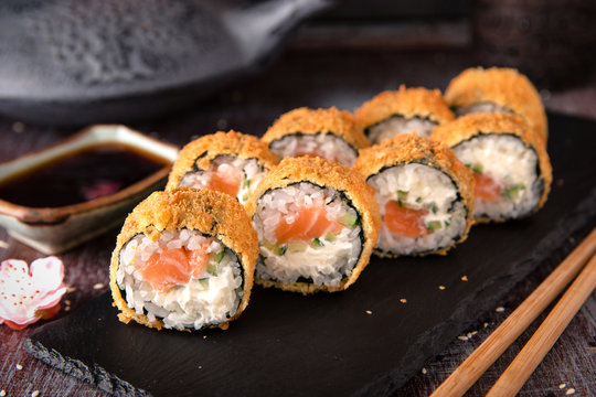 Hot fried Sushi Roll with salmon, avocado and cheese. Sushi menu. Japanese food.