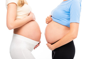 cropped view of two pregnant women showing bellies in profile isolated on white