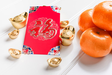 Top view Chinese New year red envelope packet ( ang pow ) with gold ingots and tangerine on white wood table top,Chinese Language on envelop mean Happiness and on ingot mean Wealthy.