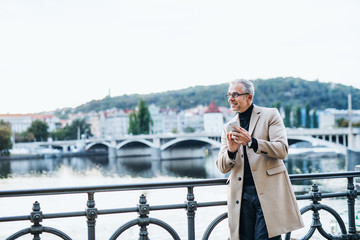 Mature businessman with smartphone standing by river in Prague city. Copy space.