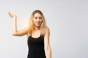 Concept portrait of a beautiful blonde girl smiling on a white background advertises product. She is right in front of the camera and shows different emotions.