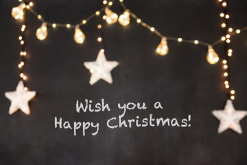 Text Wish you a Happy Christmas in black background with blurred stars and light