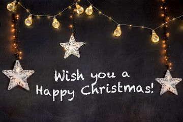 Text Wish you a Happy Christmas in black background with stars and light.