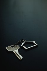 Home key with house keyring on black wood table in dark tone, real estate concept