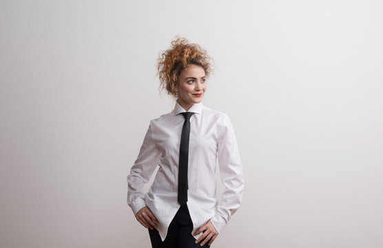 Young beautiful happy woman in studio, wearing white shirt and black tie.