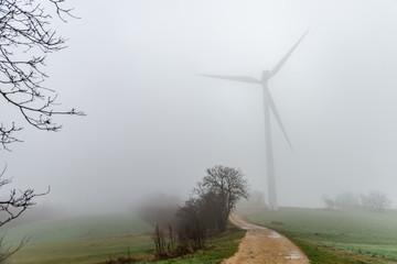 Une éolienne dans la brume du matin