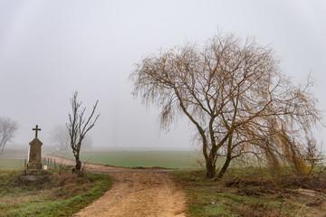 Petite stèle avec une croix et un arbre dans la brume au bord d'une route de Moselle