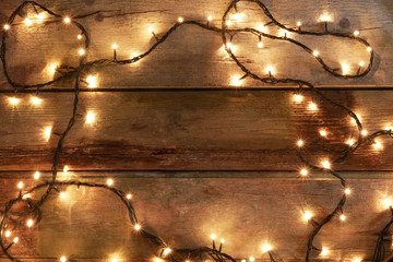 Overhead view of yellow Christmas lights spread over rustic wooden table, with copy space available in center.