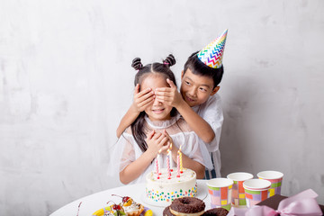 happy boy closing the girl's eyes while they are standing at the table. close up photo. gift from the heart