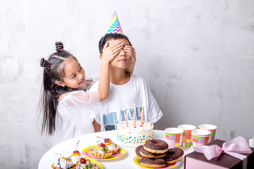 happy beautiful little girl has prepared a surprise for a brother on Birthday. event, love , holiday concept. copy space