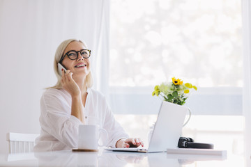 Woman talking on the phone by the laptop.