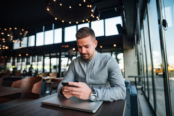 Young man texting in modern restaurant.