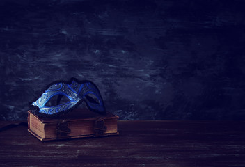 Image of elegant royal blue venetian mask over vintage old book in front dark wooden background.