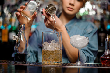 Female bartender pouring to the measuring cup with ice cubes an alcoholic drink from steel jigger