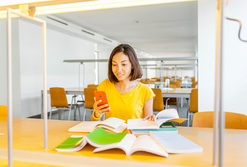 Woman student with smartphone and pile of books in university library