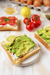 Sliced avocado on toast bread with spices on white wooden background. Food concept.
