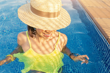 Happy asian Woman in hat nejoying vacation in swimming pool on the roof