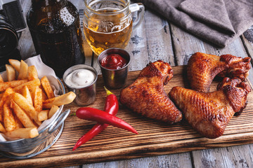 Grilled chicken wings, french fries, white and red sauce nuts on a wooden surface. Bottle and glass of beer