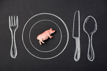 Toy pig on a plate in the figure on the chalk board