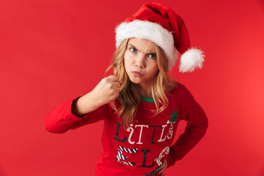 Angry little girl wearing Christmas hat standing