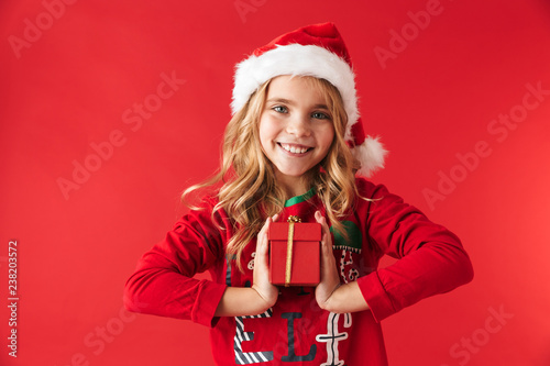 3f08fa3c736b Cute little girl wearing Christmas hat standing