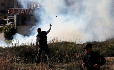 Palestinian hurls stones during clashes with Israeli forces in Ramallah in the occupied West Bank