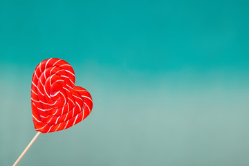 Valentine's day background. Lollipop in shape of heart on turquoise blue background. Concept for Valentine's Day or wedding day